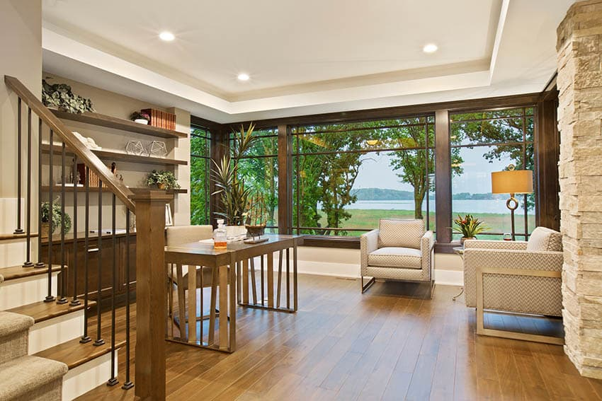 Contemporary home office with hardwood flooring and built in bookshelves with lake views