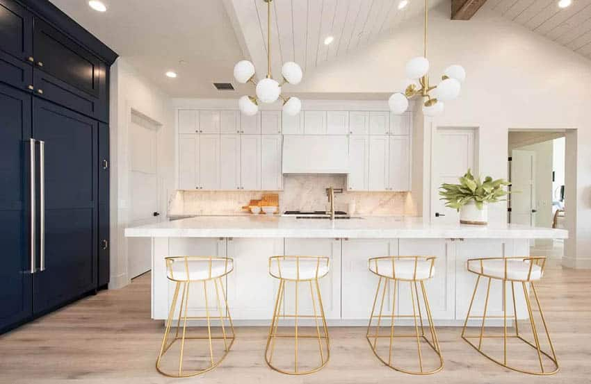 Contemporary kitchen with dark and light cabinets, white quartz countertops, light wood flooring and gold bar stools