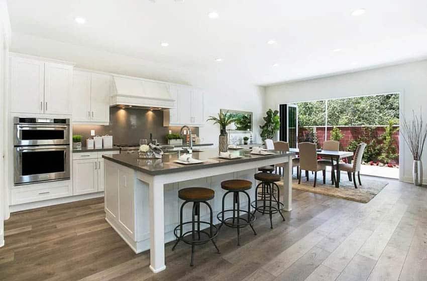 Contemporary kitchen with dark gray quartz countertops gray backsplash white shaker cabinets dark wood flooring