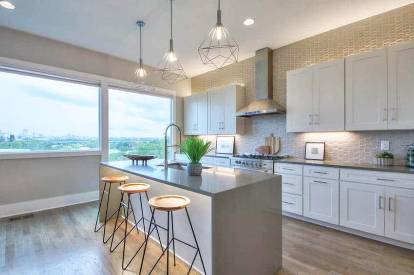 Contemporary kitchen with gray quartz countertops white cabinets under cabinet lighting tile backsplash