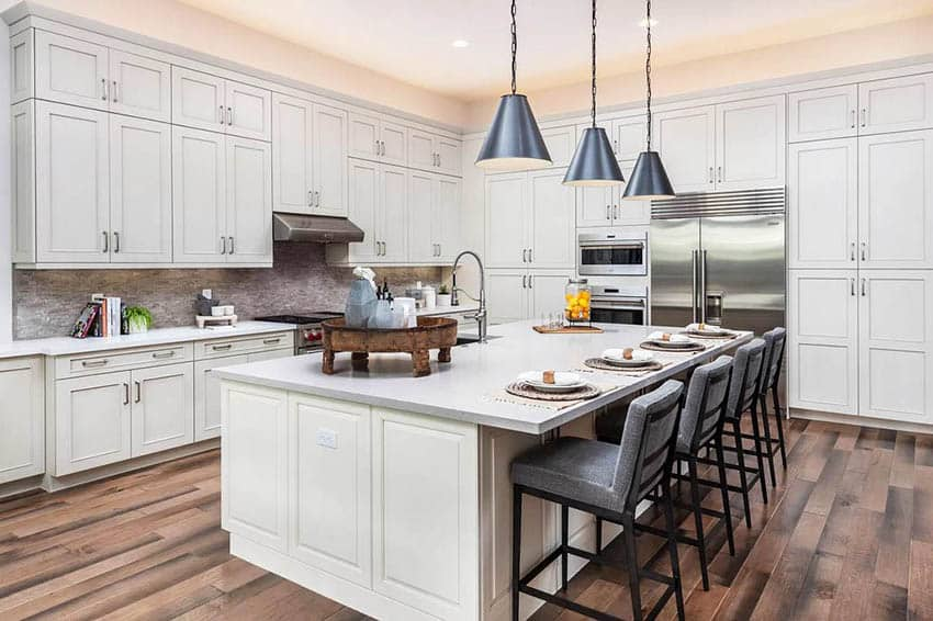 Contemporary kitchen with white cabinets off white quartz countertops wood flooring