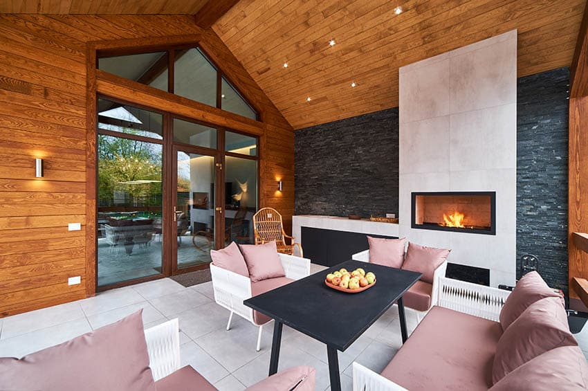 Covered patio with gas fireplace with glass screen and stacked stone accent wall