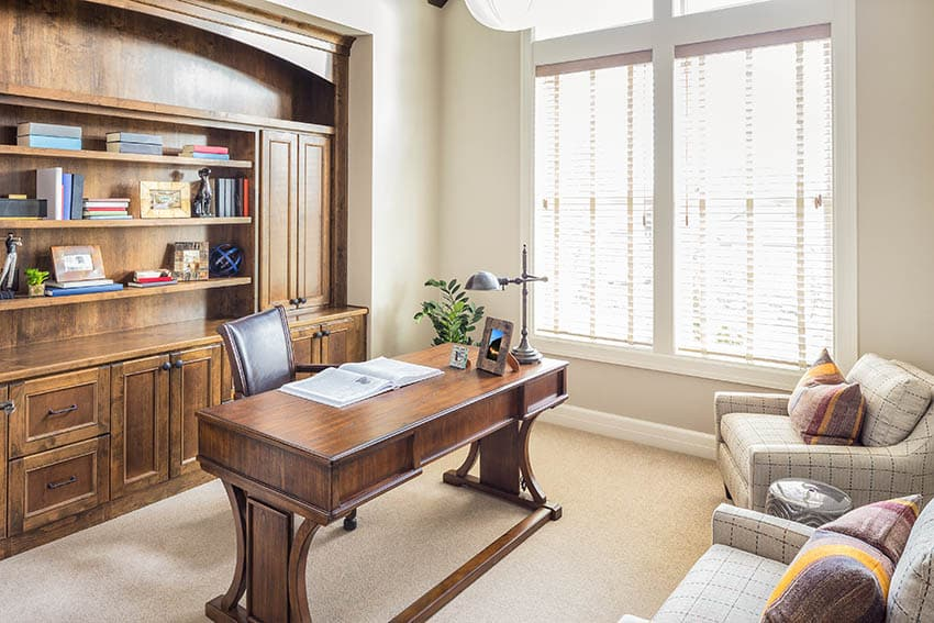 Home office with broadloom carpet and wood built-in bookshelves