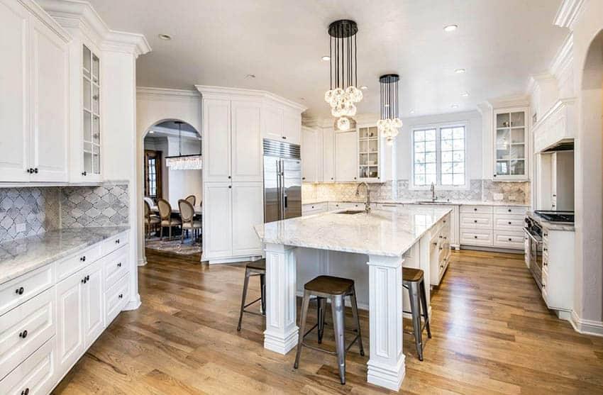 Kitchen with marble countertops arabesque tile backsplash white cabinets