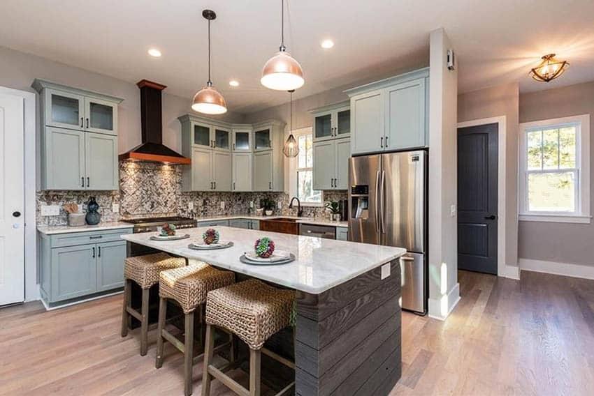Kitchen with quartzite countertops light green cabinets dark wood island