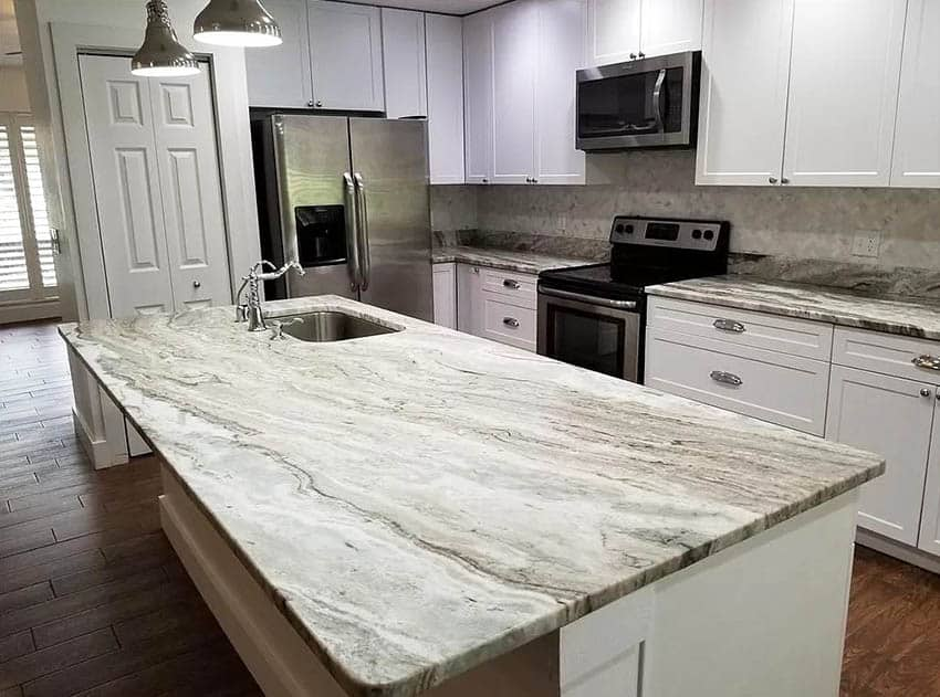 Kitchen with quartzite slab countertop island white cabinets