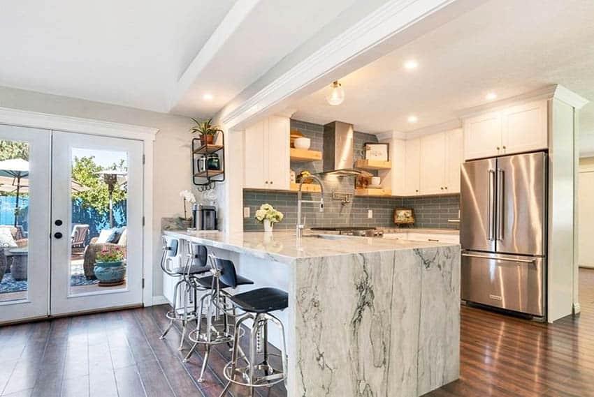 Kitchen with quartzite waterfall countertop peninsula gray tile backsplash white cabinets