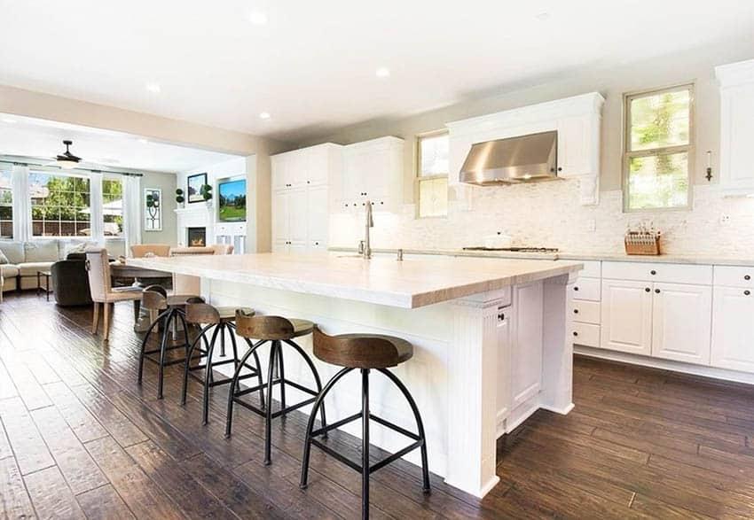 Kitchen with taj mahal quartzite countertops white cabinetry hand scraped wood flooring