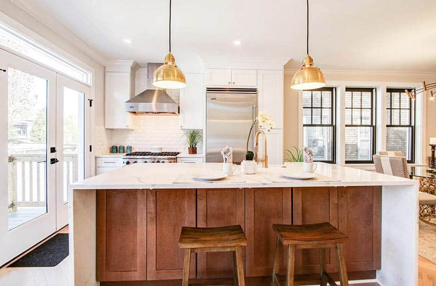 Kitchen with white cabinets brown wood island white quartzite countertops gold pendant lights