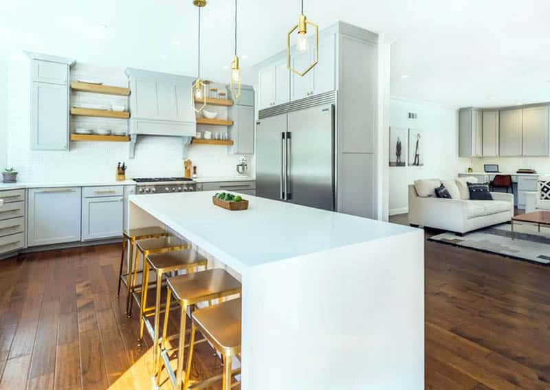Kitchen with white quartz waterfall island gray shaker style cabinets