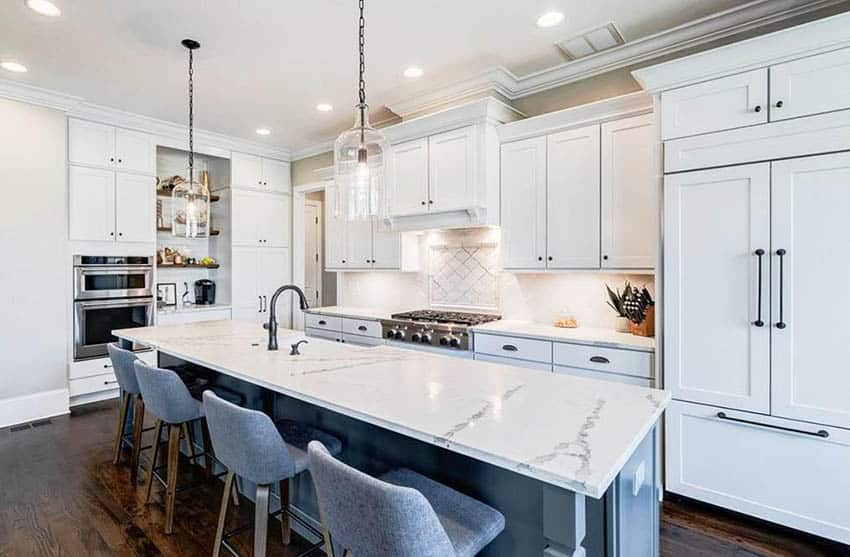 Kitchen with white quartz with gray veining countertops white cabinets gray island