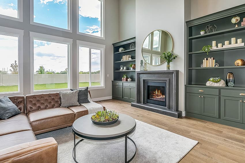 Living room with gas fireplace with dark mantel and green built-in cabinets