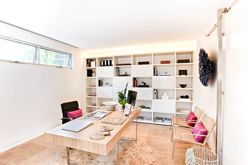 Modern home office with limestone flooring wall of shelving