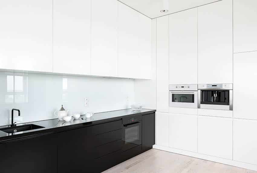 Modern kitchen with black glass countertops white and black cabinets