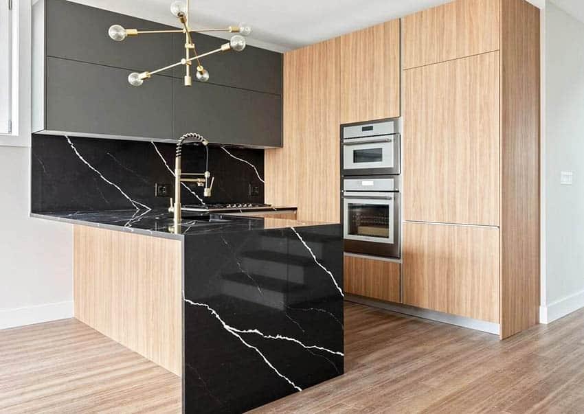 Modern kitchen with two tone cabinets, black waterfall quartz peninsula, modern chandelier and light wood flooring