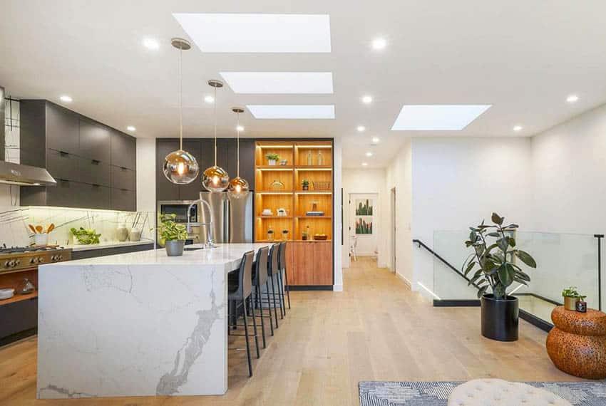 Modern kitchen with waterfall quartz countertop island dark gray cabinets