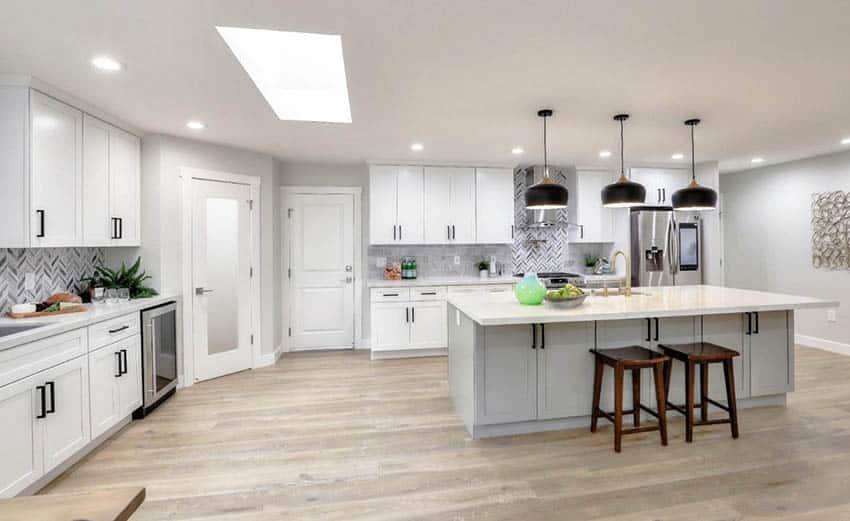 Open concept kitchen with quartz countertops skylight white cabinets gray island