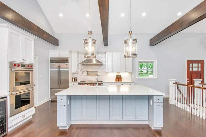 Open plan kitchen with white quartzite countertops white cabinets wood beam ceiling