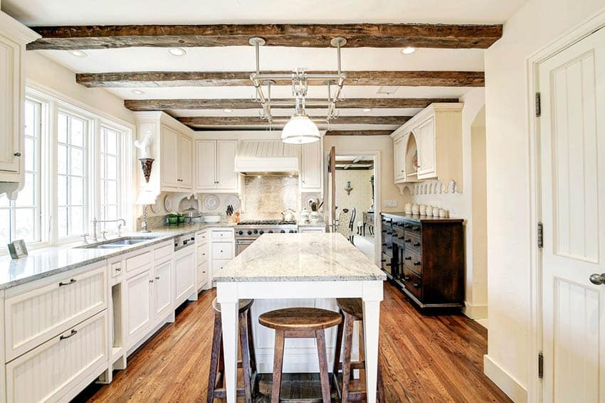 Remodeled cape cod kitchen with white cabinets, beadboard doors and exposed beam ceiling