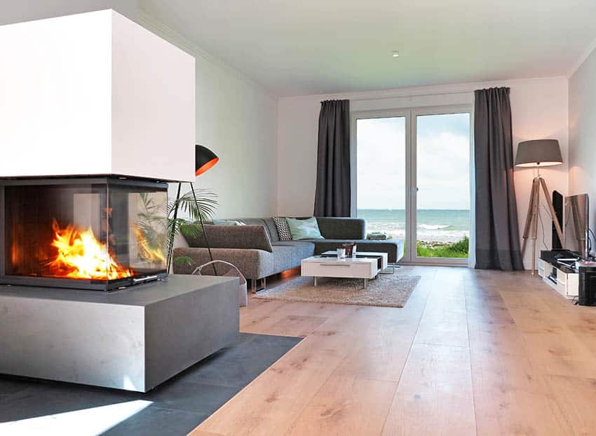 Three sided gas fireplace in modern living room with ocean views