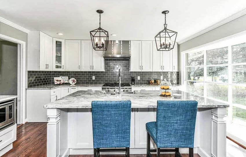Transitional kitchen with black and white quartzite countertops black subway tile white cabinets