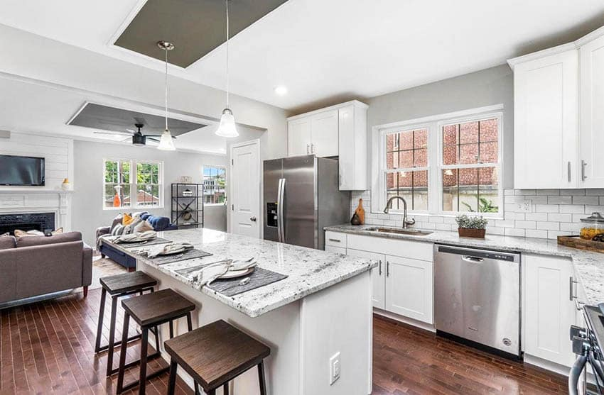 Transitional kitchen with white granite countertops white cabinets subway tile and gray paint