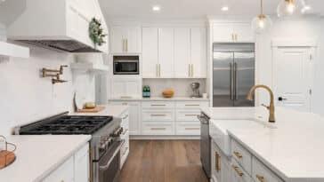 Beautiful kitchen with white shaker style cabinets gold hardware white quartz countertops