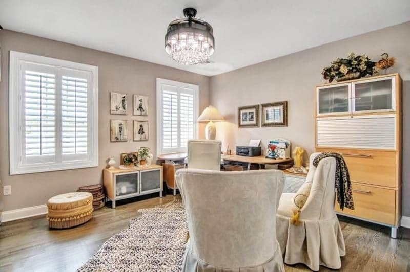 Craft room with light brown paint and comfy seating plantation shutters