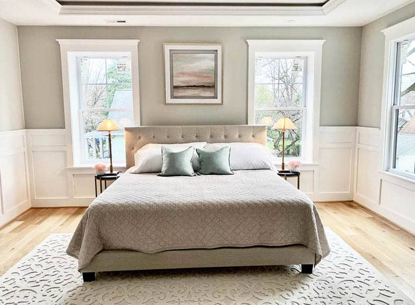 Farmhouse bedroom with king bed white wainscoting white window frames light gray paint