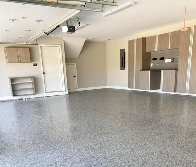 Garage with gray epoxy flooring cabinet storage