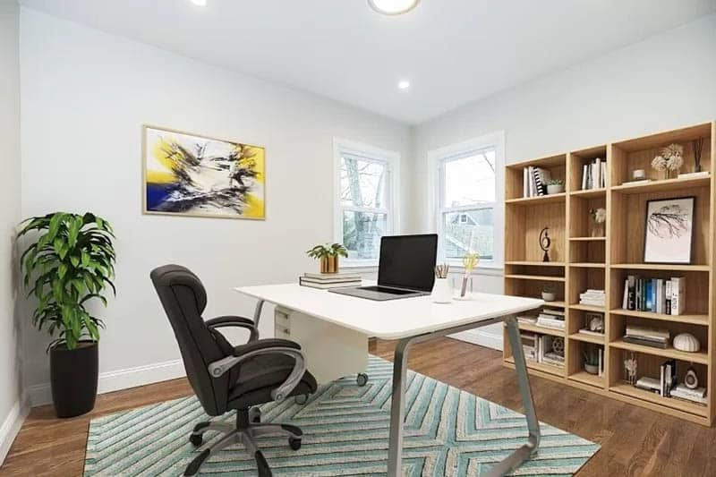 Home office with wood flooring area rug and shelving