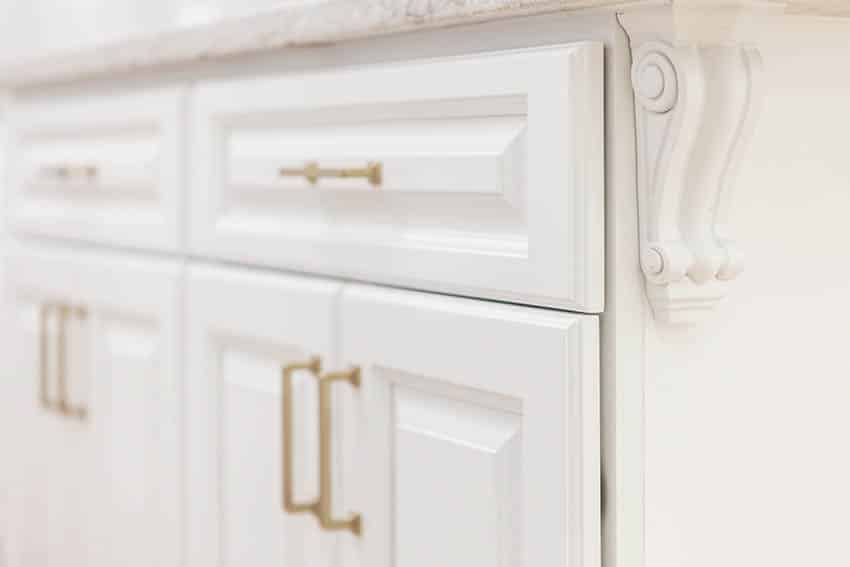 Kitchen raised panel cabinets with gold hardware close up