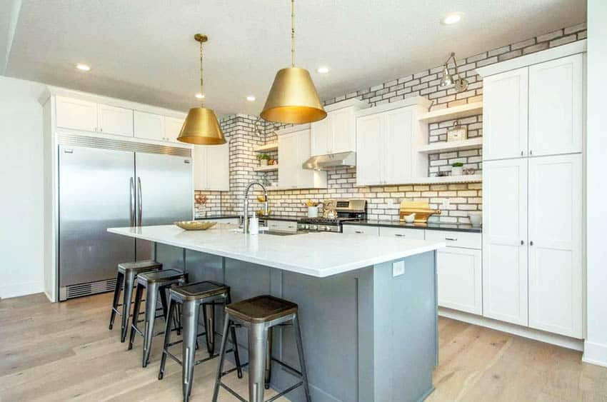 Kitchen with white cabinets gray island gold pendant lights and hardwood floors