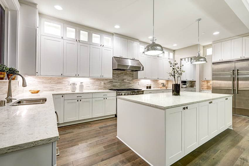 Kitchen with white shaker cabinets light color marble countertops chrome pendant lighting wood floors