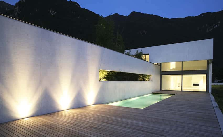 Modern home with plaster walls by swimming pool