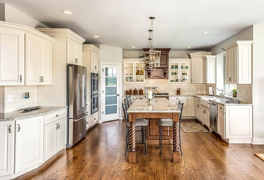 Traditional kitchen with raised panel style cabinets cream cabinets dark wood island pantry door