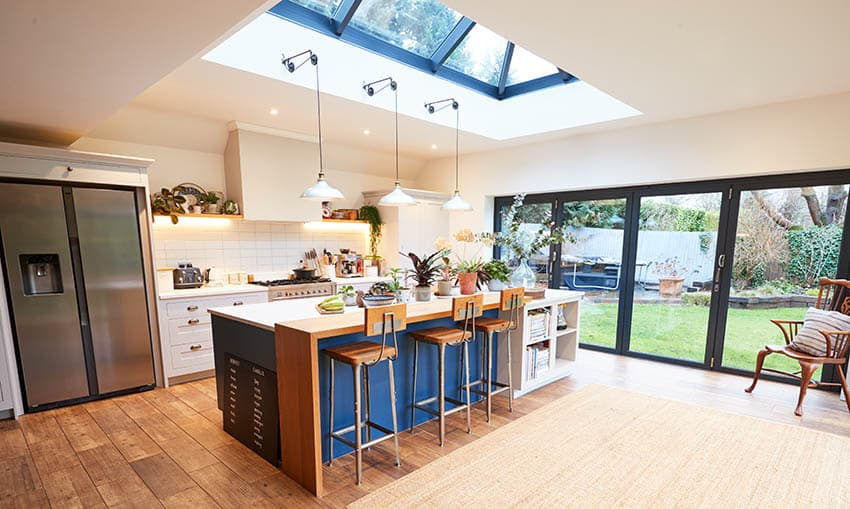 Bright kitchen design with skylight large sliding door and blue island with wood breakfast bar