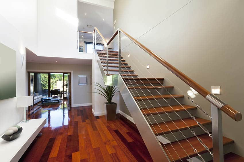 Cherry wood floating stairs with stainless steel supports and polished wood hand rail