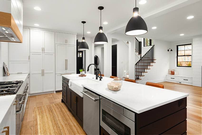 Contemporary kitchen with apron sink in island with white quartz countertops black pendant lights