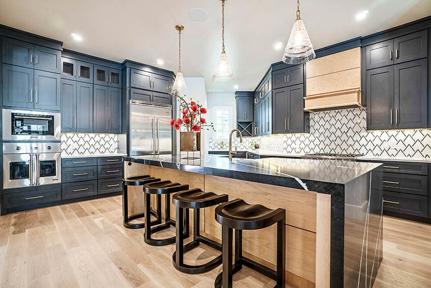 Contemporary kitchen with geometric tile backsplash black cabinets black quartz waterfall countertop pendant lights