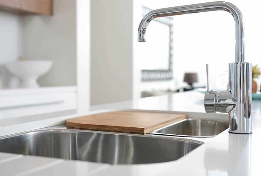 Double basin kitchen sink with 1 smaller bowl and cutting board