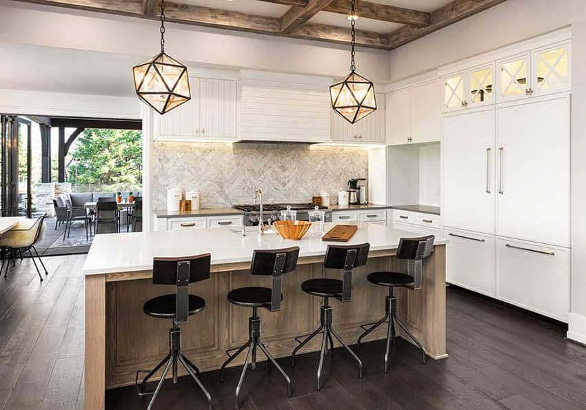 Kitchen with marble backsplash and countertops wood beams
