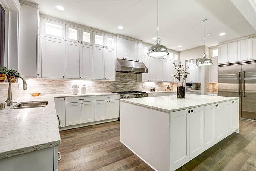 Kitchen with mosaic tile backsplash white shaker cabinets light color marble countertops chrome pendant lighting wood floors