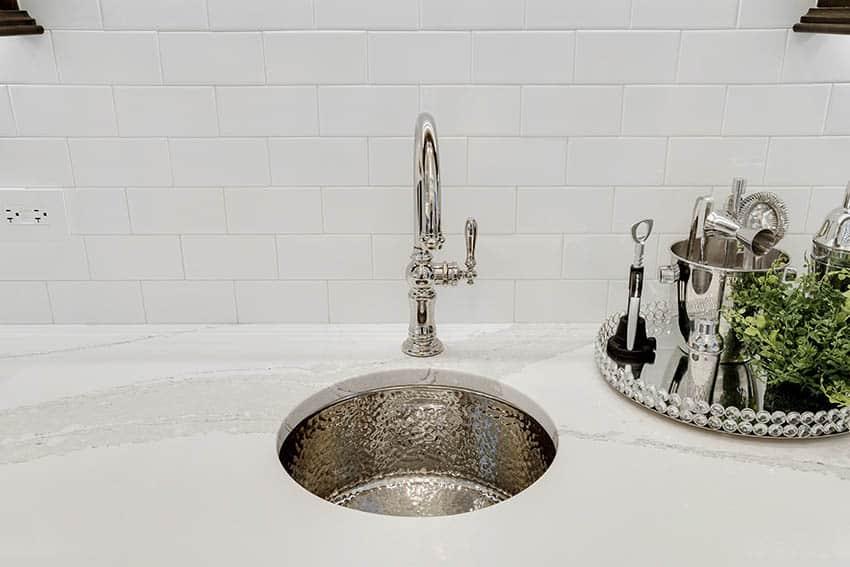 Kitchen with porcelain subway tile backsplash hammered chrome sink