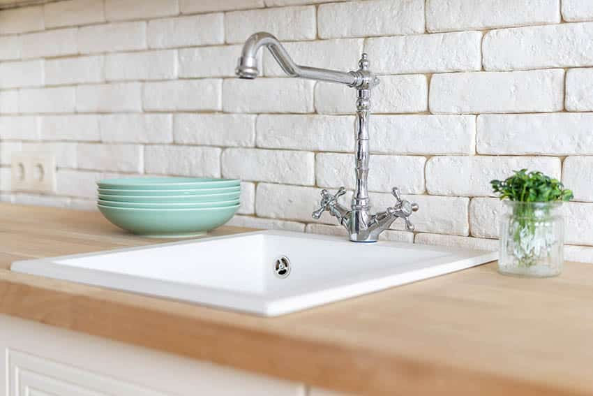 Kitchen with stone backsplash single basin sink wood countertop