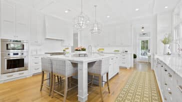 Kitchen with timeless white cabinets, marble countertops and wood flooring