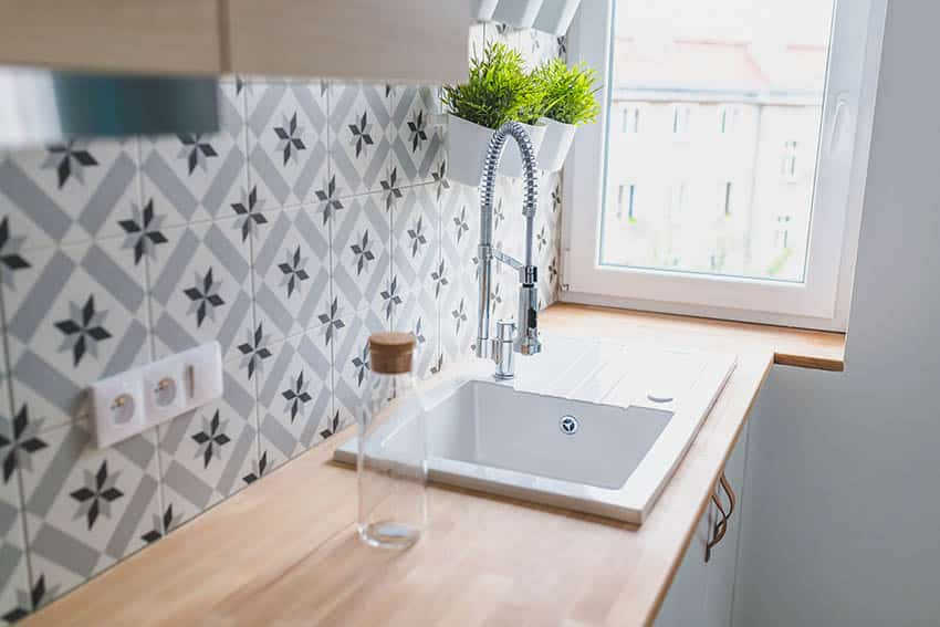 Kitchen with touchless faucet and spanish tile backsplash