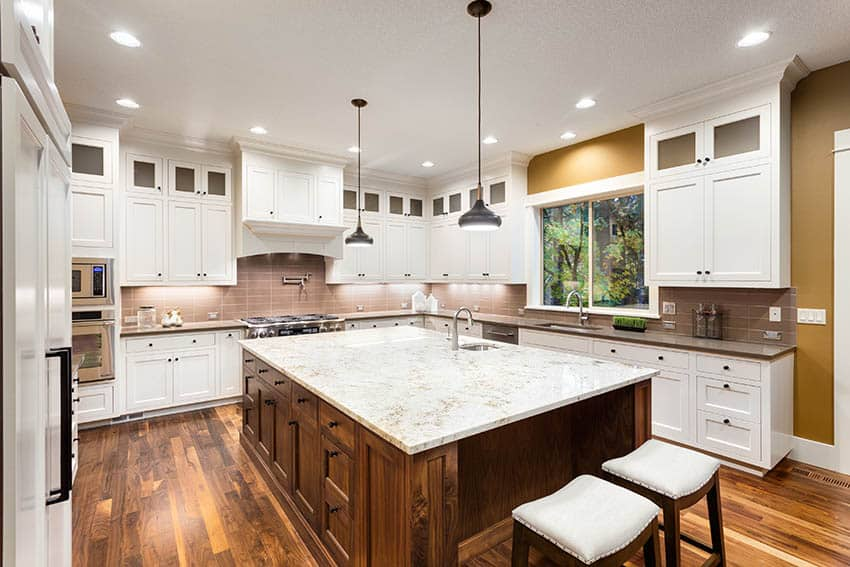 Kitchen with white granite countertops white cabinets brown island and two sinks