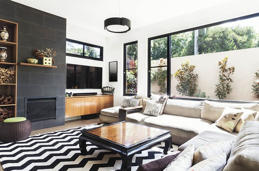 Modern black white living room with black tile fireplace and floating wood mantel