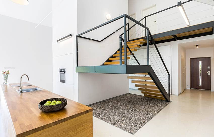 Modern floating staircase with black hand rails bright wood steps